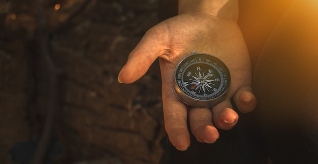 Hand met kompas, navigatie in bos, natuur, reizen en avontuur achtergrondfoto