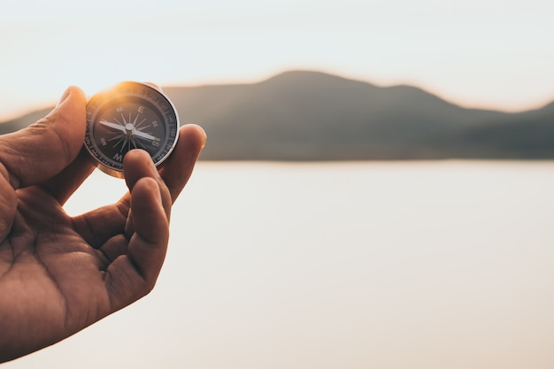 Hand met kompas op bergweg bij zonsonderganghemel