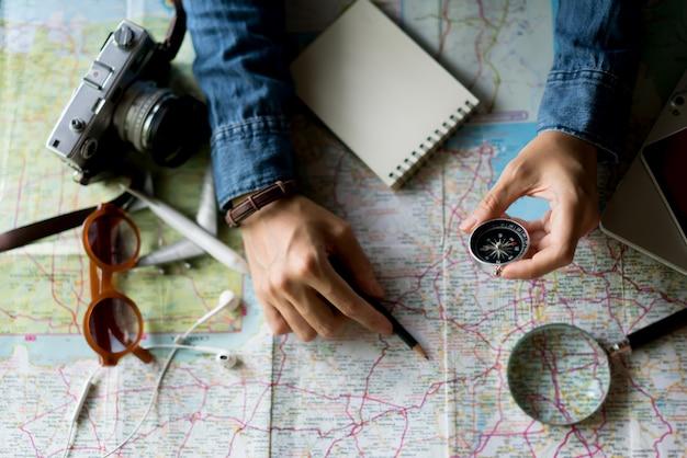 Hand met kompas voor het plannen van vakantiereis en accessoires voor reizen