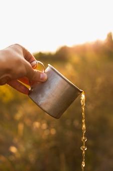 Hand met kop gieten drankje
