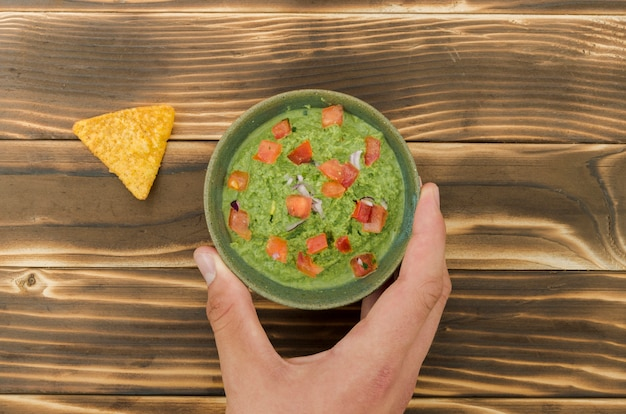 Hand met kopje garneer in de buurt van nacho