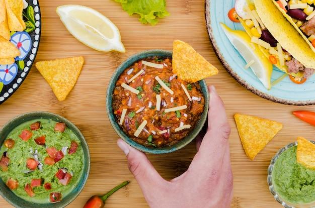 Hand met kopje garneer met nacho in de buurt van mexicaans eten