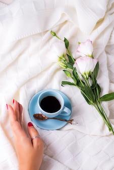 Hand met kopje koffie met chocolade, bloemen eustoma op deken in bed.