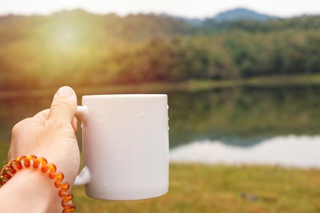 Hand met kopje met gestoomde hete koffie in de herfst natuur landschap met herfstbladeren en zonlicht.