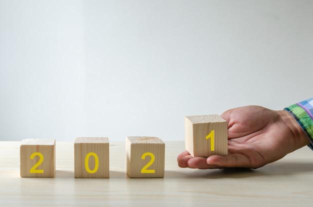 Hand met kubussen gelukkig nieuwjaar 2021 pictogrammen. bedrijfsconcept