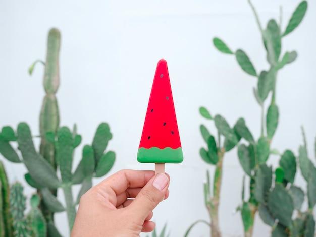 Hand met kunstmatige watermeloen plak ijslolly op groene cactustuin en witte muur achtergrond. ijsstokje met zomerfruit.
