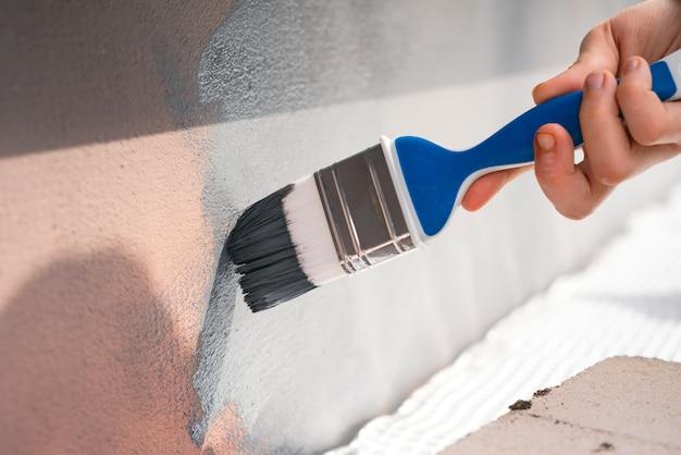 Hand met kwast schilderen gebouw buitenmuur