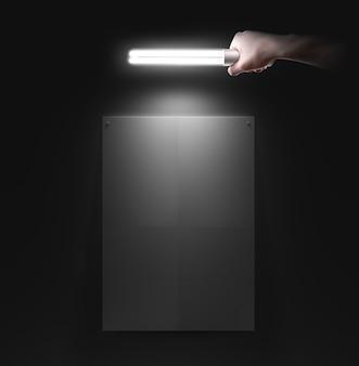 Hand met lamp in de buurt van de muur met lege poster