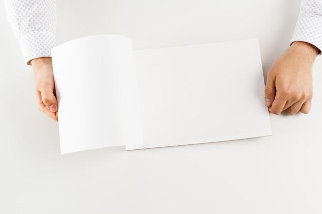 Hand met lege geopende boek mock up