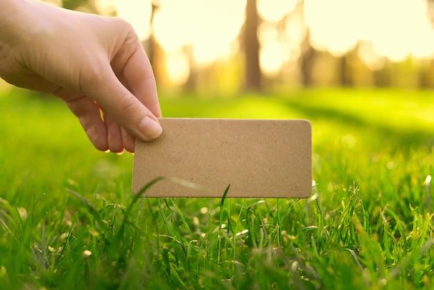 Hand met lege kaart in een park in zonnige stralen. muur. kopieer ruimte.