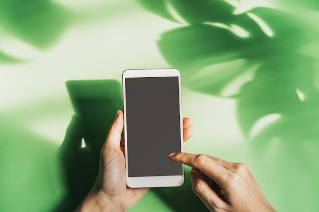 Hand met lege scherm slimme telefoon met schaduw van tropisch verlof