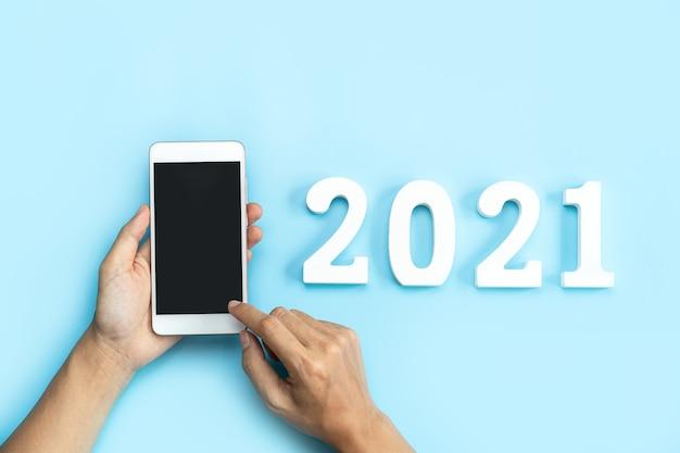 Hand met lege scherm slimme telefoon op blauw met nieuwjaarsconcept 2021 en kopie ruimte