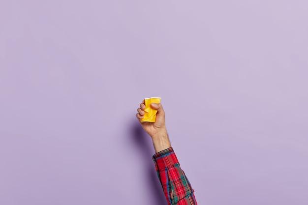 Hand met lege verfrommelde kop koffie over paars