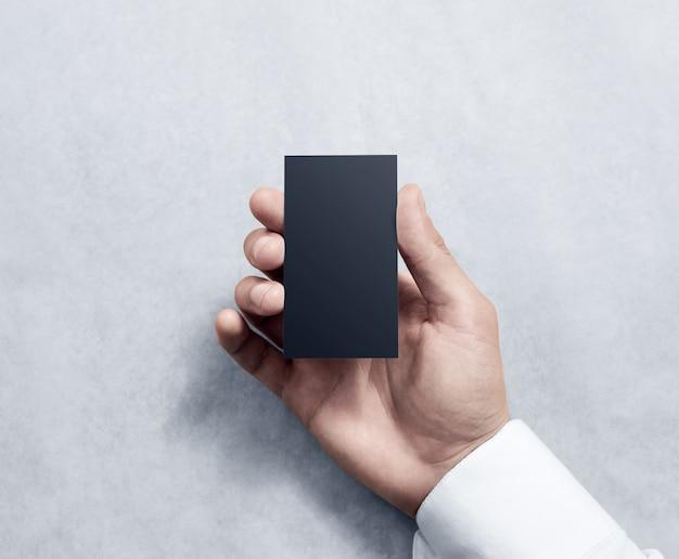 Hand met lege verticale zwarte visitekaartje ontwerp