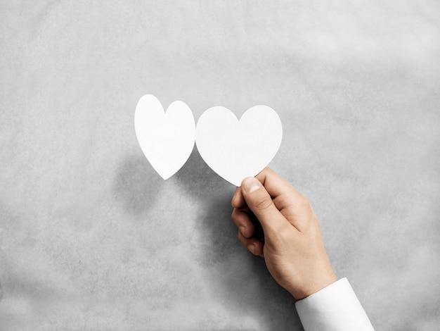 Hand met lege witte valentijnsdag kaart mockup