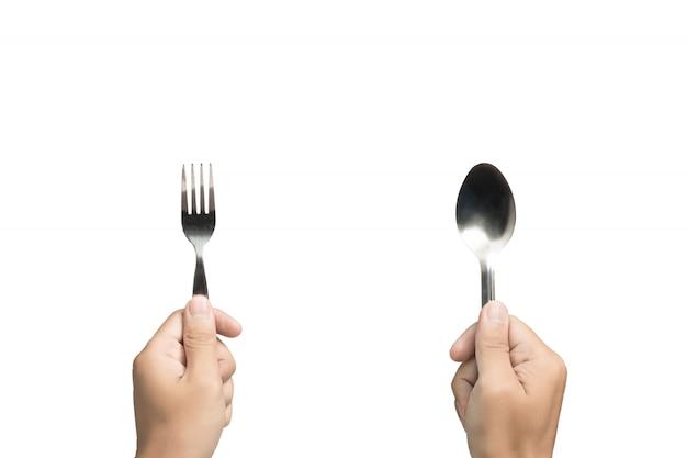 Hand met lepel en vork op geïsoleerde achtergrond.