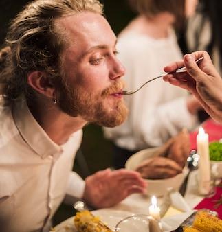 Hand met lepel voedende man bij het diner