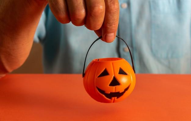 Hand met mand met halloween pompoen snoepjes. ruimte kopiëren. selectieve aandacht.