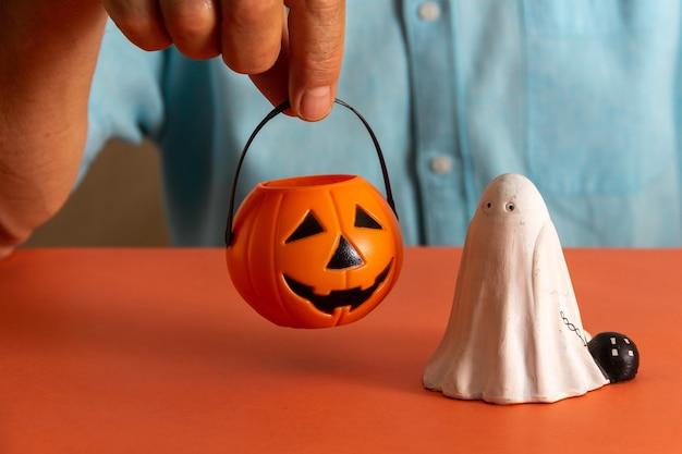Hand met mand met halloween-pompoensnoepjes en spook. ruimte kopiëren. selectieve aandacht.