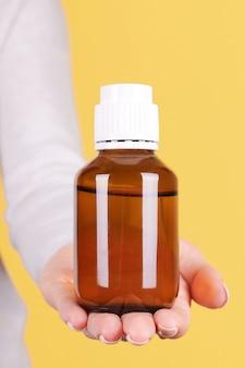 Hand met medicijnfles, geïsoleerde chemiecontainer