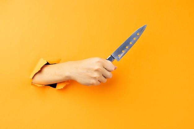 Hand met mes dat uit de muur steekt Premium Foto