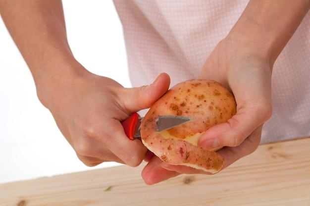 Hand met mes peeling aardappel plantaardig voedsel.