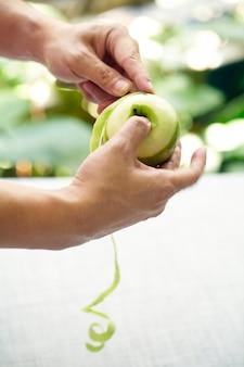 Hand met mes peeling appelhuid