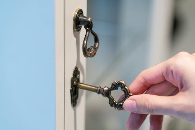 Hand met metalen vintage sleutel om te ontgrendelen.