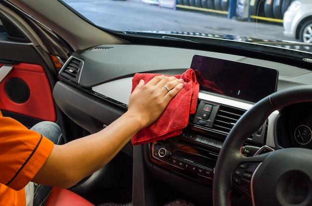 Hand met microfiber doek schoonmaken auto-interieur