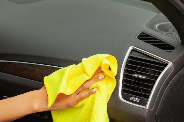 Hand met microfiber doek schoonmaken moderne auto interieur.