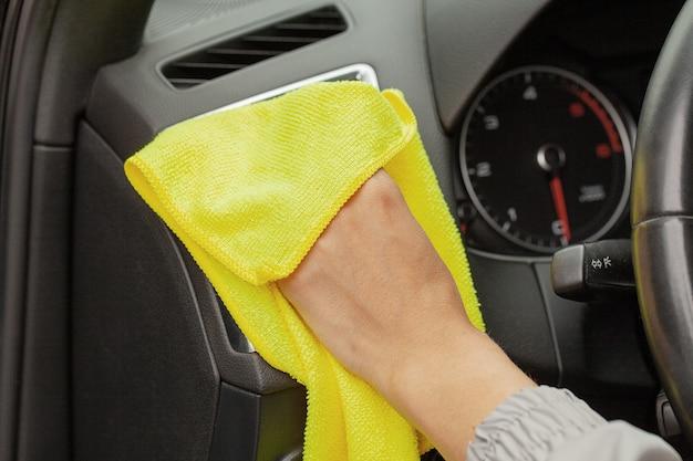 Hand met microfiber doekje schoonmaken interieur moderne auto.