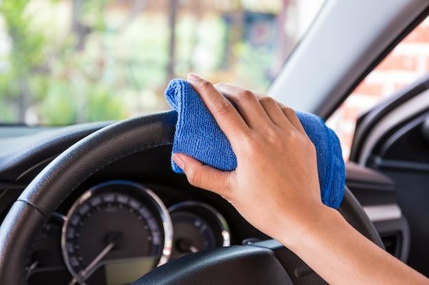 Hand met microfiber doekreiniging interieur en moderne auto op stuurwiel.