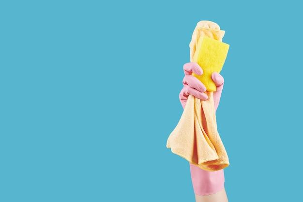 Hand met microvezeldoek en spons