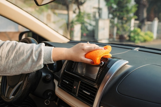 Hand met microvezeldoekreinigingsstoel, auto-detaillering en parkeerconcept, auto-interieur wassen, selectieve focus