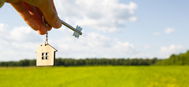 Hand met miniatuurhuis en sleutels