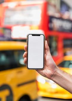 Hand met mobiel op onscherpe achtergrond