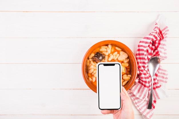 Hand met mobiel op tafel met voedselplaat