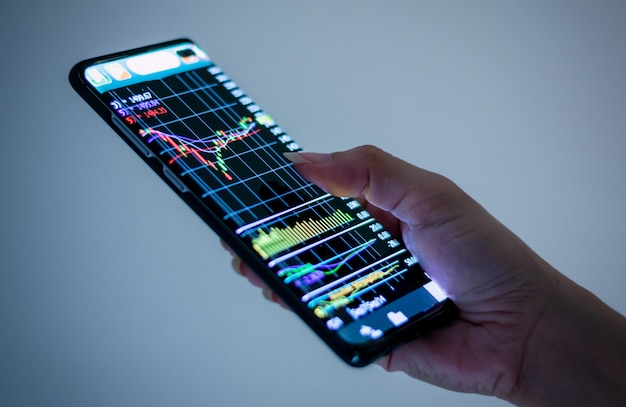 Hand met mobiele telefoon bedrijfstechnologie, grafiek, financiële en aandelenmarkt