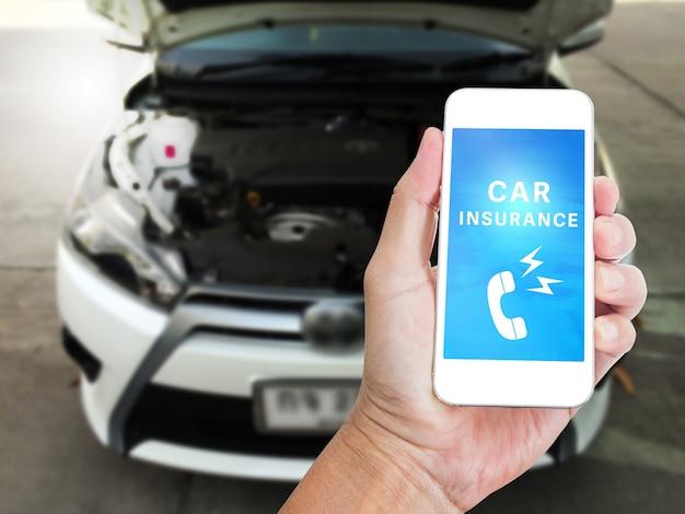 Hand met mobiele telefoon met autoverzekering woord met auto interieur achtergrond wazig, digitale auto concept