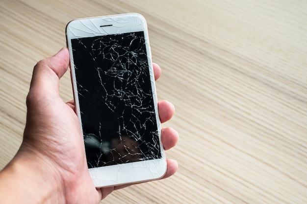 Hand met mobiele telefoon met gebroken glas scherm