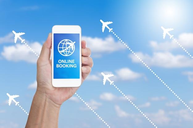 Hand met mobiele telefoon met online boeking woord op wolk en blauwe hemelachtergrond
