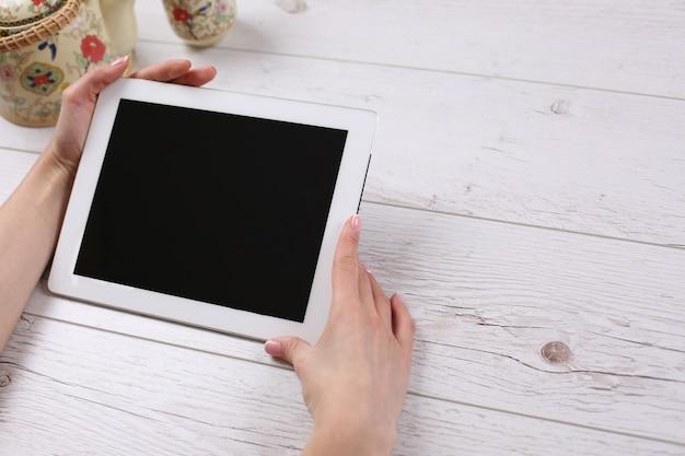 Hand met mockup-tablet vergelijkbaar met ipad-stijl op houten tafel met display