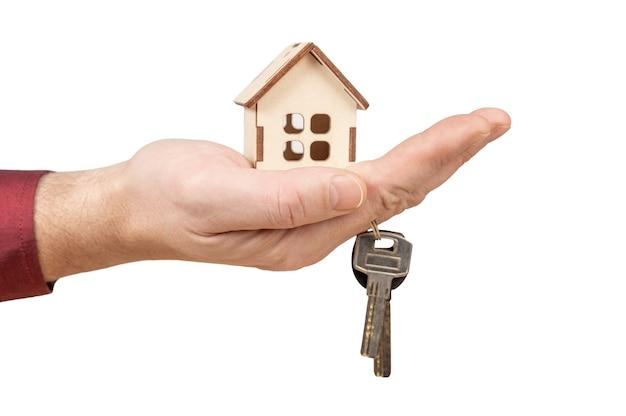 Hand met model huis en sleutels. hypotheeklening goedkeuring woningkrediet en verzekeringsconcept.