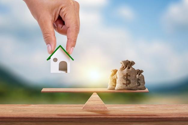 Hand met model van huis en spaarzak geplaatst op schalen en wazig groene achtergrond