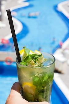 Hand met mojito-cocktail op de achtergrond van het zwembad