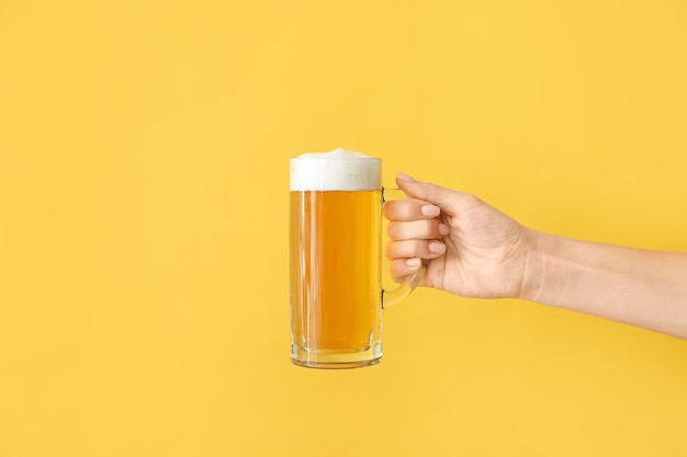 Hand met mok bier op kleur