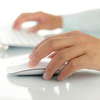 Hand met muis en toetsenbord van de computer