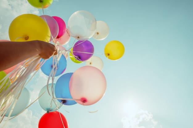 Hand met multi gekleurde ballonnen