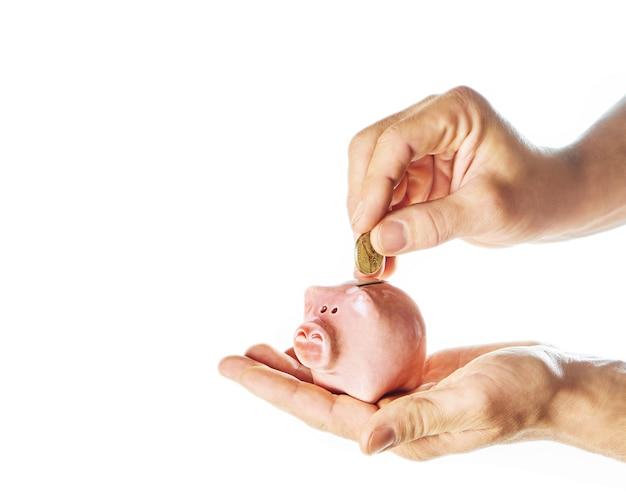 Hand met muntstuk over een spaarvarken op witte achtergrond met bezinning