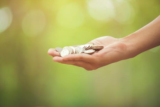 Hand met muntstukken op bokehachtergrond. het concept van het geldgeld zachte nadruk